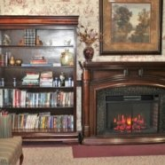 Fireplace and bookshelf inside the cozy living room at Mt Hope Nursing Center