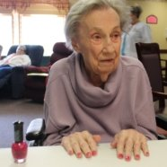 Photo of a resident with her hands on the table getting her nails painted red