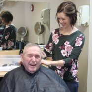 Resident getting his hair cut with hair stylist. Both are laughing