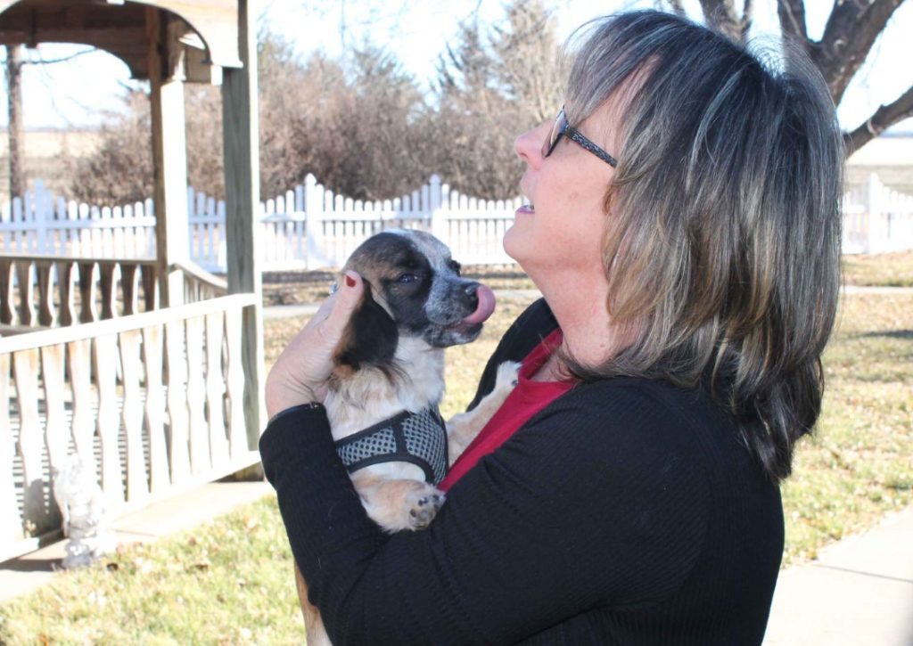 Photo of puppy Jasper being held by his owner, administrator of Mount Hope Nursing Center