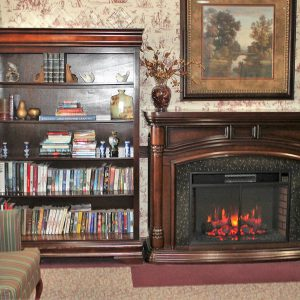 fireplace and book shelf in the cozy setting at Mt Hope Nursing Center
