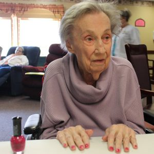Mt Hope resident with newly polished red nails sitting in a community space