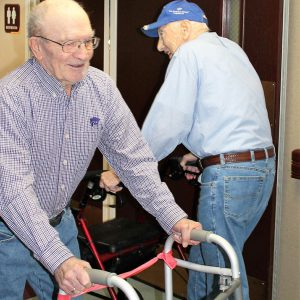 two smiling residents of Mt Hope walking down our hallway