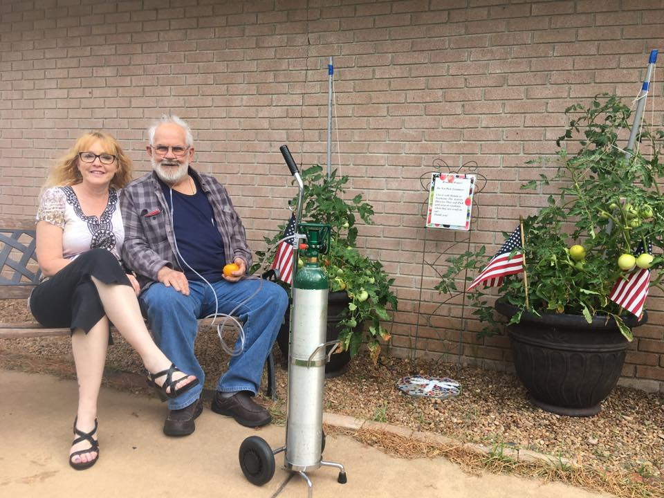Photo of nursing home resident and staff sitting by outside container garden