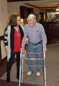 Patient and staff walking down nursing home hallway at Mount Hope Nursing Center