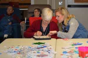 Photo of a young lady helping a senior woman with a craft project at Mount Hope Nursing Center