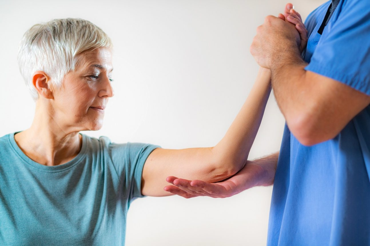 An aging woman receiving physical therapy on her arm by a licensed therapist