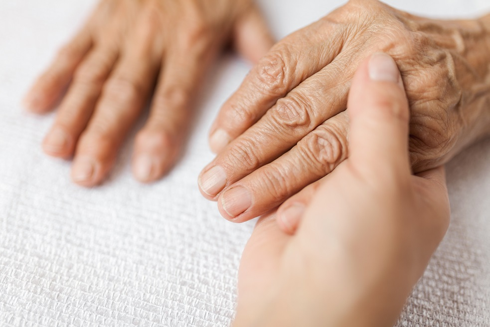 Caretaker hands holding the hands of an older person, regarding concerns of financial abuse