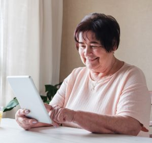 Elderly woman reading on an ipad, an excellent Father's Day gift for a senior citizen