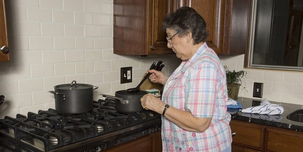 An elderly person cooking in a safe kitchen